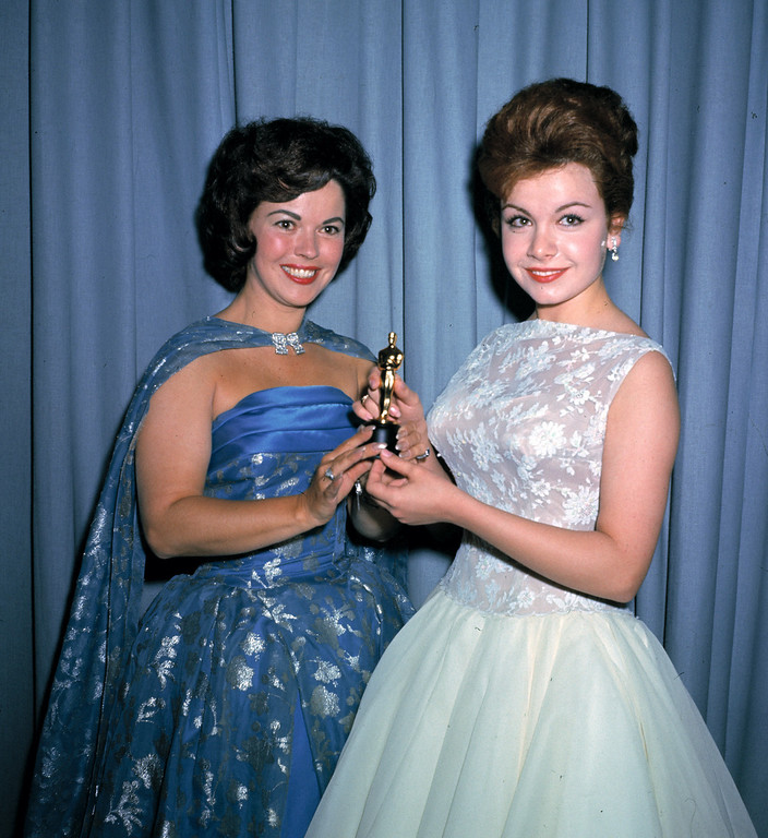 Description of . Actress Annette Funicello, right, and former child film star Shirley Temple, left, are seen holding a miniature Oscar statuette at the annual Academy Awards presentations, in Los Angeles, Calif., in April 1961. (AP Photo/Brich)