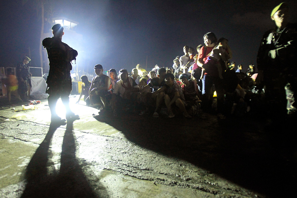 Description of . Soldiers watch over Typhoon Haiyan survivors as they wait for the last evacuation flight at the airport in Tacloban, central Philippines, Thursday, Nov. 14, 2013.  (AP Photo/Wally Santana)