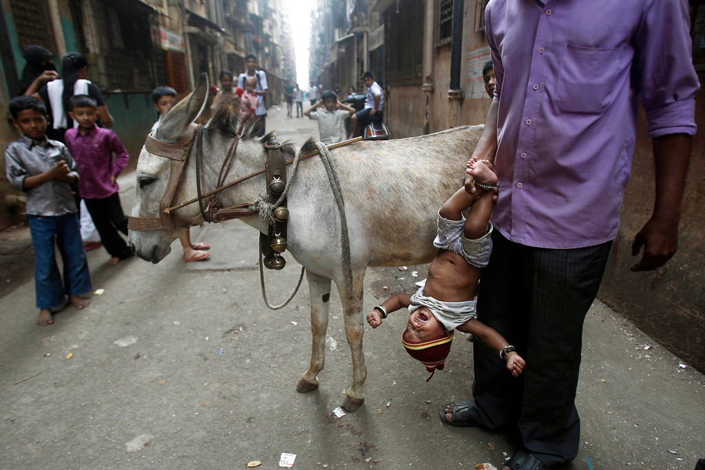 Description of . In this Feb. 29, 2012 file photo, Santosh, who sells donkey milk, holds a baby upside down after feeding him some of the liquid, locally believed to be a cure for a persistent cough in a slum in Mumbai, India. Millions of children are growing up in squalid urban areas and denied basic services despite living close to them. UNICEF said children living in slums and shantytowns often lack water, electricity and healthcare and urged policy makers to ensure urban planning meets the needs of children. (AP Photo/Rafiq Maqbool, File)