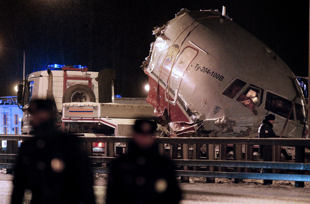Description of . A truck removes the cabin of the Tu-204 jet from its crash site near the Vnukovo airport outside Moscow on December 29, 2012. Four crew were killed when a Russian airliner crashed into a motorway and broke up into three pieces after overshooting the runway at an international Moscow airport. The Red Wings airlines Russian-made Tu-204 jet -- empty of passengers and carrying just its eight crew on a return trip from the Czech Republic -- caught fire after crashing through the perimeter fence of Vnukovo airport in the west of the city.  NATALIA KOLESNIKOVA/AFP/Getty Images