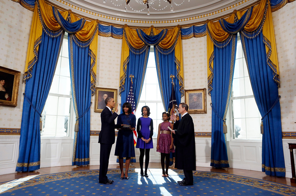 Description of . President Barack Obama is officially sworn-in by Chief Justice John Roberts in the Blue Room of the White House during the 57th Presidential Inauguration in Washington, Sunday, Jan. 20, 2013. Next to Obama are first lady Michelle Obama, holding the Robinson Family Bible, and daughters Malia and Sasha. (AP Photo/Larry Downing, Pool)
