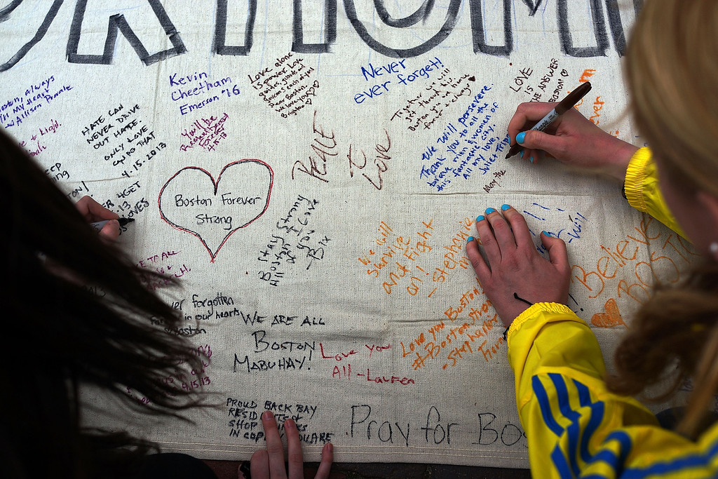 Description of . BOSTON, MA - APRIL 16: People write messages on a memorial canvas during a vigil for victims of the Boston Marathon bombings at Boston Commons on April 16, 2013 in Boston, Massachusetts. The twin bombings, which occurred near the marathon finish line, resulted in the deaths of three people while hospitalizing at least 140. The bombings at the 116-year-old Boston race, resulted in heightened security across the nation with cancellations of many professional sporting events as authorities search for a motive to the violence.  (Photo by Spencer Platt/Getty Images)