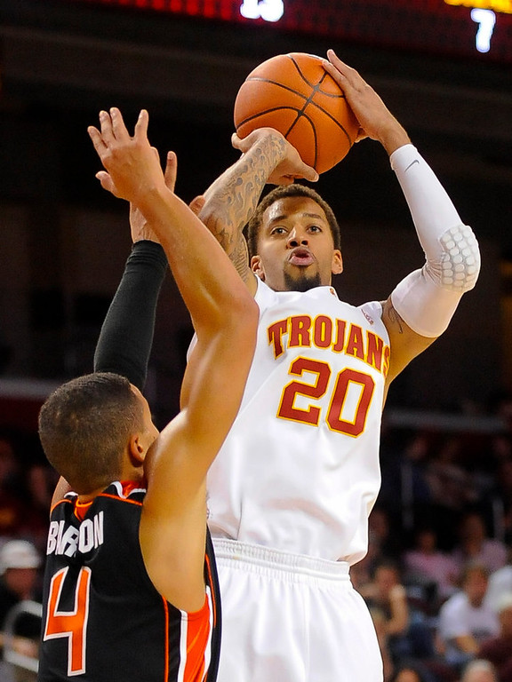 Description of . Southern Cal guard J.T. Terrell (20) shoots over Oregon State guard Challe Barton (4) during the second half of an NCAA college basketball game, Saturday, Jan. 19, 2013, in Los Angeles. Southern Cal won 69-68. (AP Photo/Gus Ruelas)