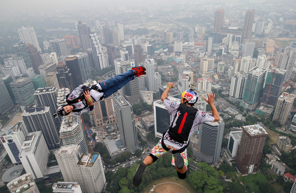 Description of . Base jumper Jean-Philippe Marie Teffaud, left, and his team mate Frederic Yves Fugen of France leap from the 300-meter Open Deck of the Malaysia's landmark Kuala Lumpur Tower during the International Tower Jump in Kuala Lumpur, Friday, Sept. 27, 2013. (AP Photo/Vincent Thian)
