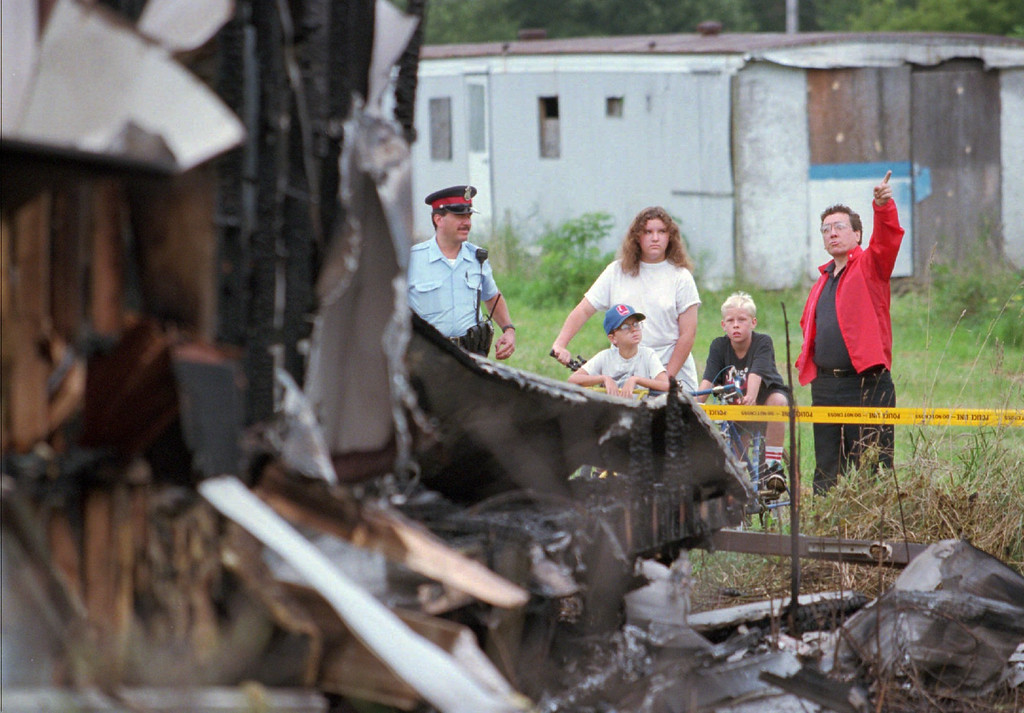 Description of . John Stephenson, right, points toward the sky as he and others examine the wreckage of a mobile home apparently destroyed by a meteor in Windsor, Ontario early Friday, morning, Aug. 25, 1995. Windsor police said a chunk of the meteor slammed into the vacant mobile home, burning it to the ground. No injuries were reported. Others in photo are Windsor police Sgt. Joseph Monteleone, left, Tanya Neufeld, 12, her brother, Kevin, 11, and Matthew Breault, 11, all residents of the park. (AP Photo/Tom Pidgeon)