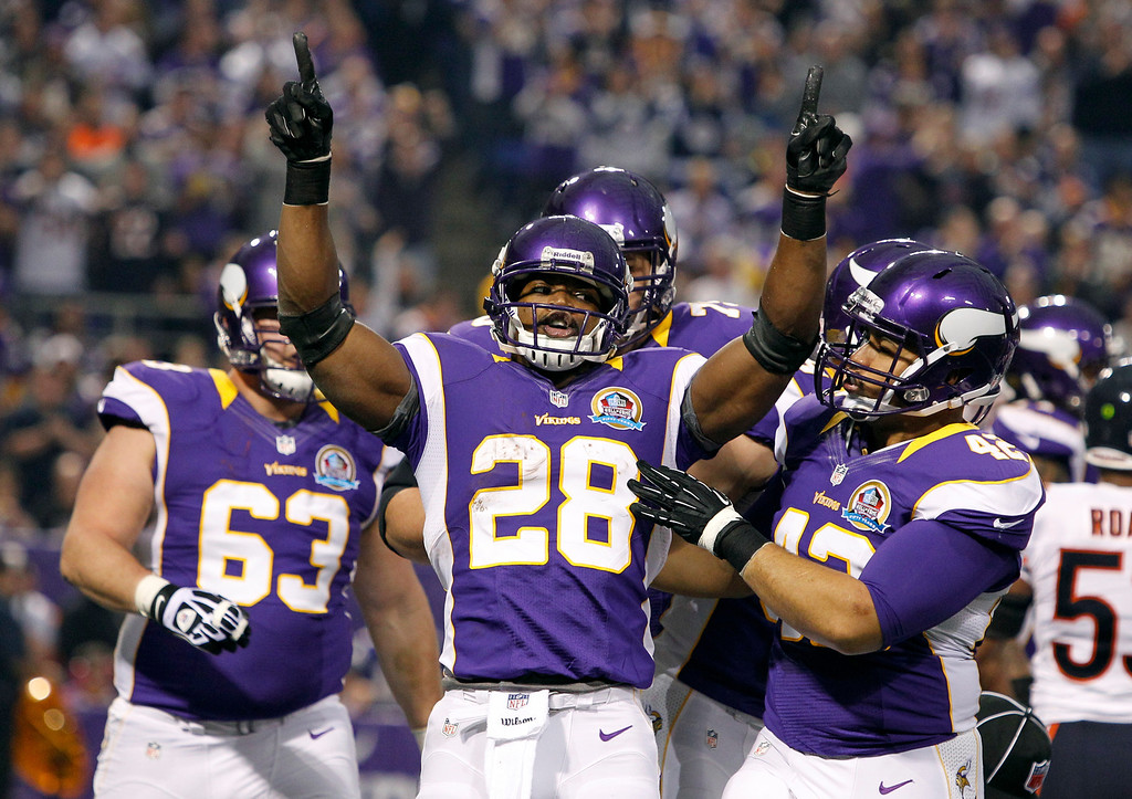Description of . Minnesota Vikings running back Adrian Peterson (28) celebrates with teammate Jerome Felton, right, after scoring on a 1-yard touchdown run during the first half of an NFL football game against the Chicago Bears Sunday, Dec. 9, 2012, in Minneapolis. (AP Photo/Genevieve Ross)