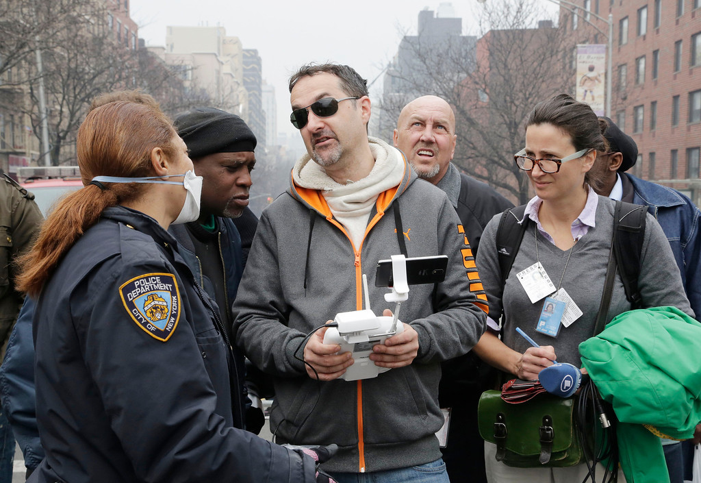 Description of . A New York City police officer, left, tells Brian Wilson, center, to land the drone that he was flying over the scene of an explosion that leveled two apartment buildings in East Harlem, Wednesday, March 12, 2014 in New York. Wilson says he uses the aerial drone to document buildings, weddings and news events. (AP Photo/Mark Lennihan)