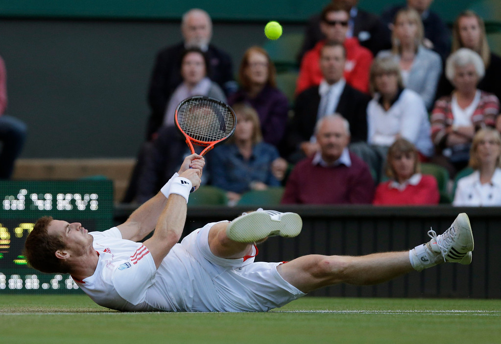Description of . In this June 30, 2012 file photo, Andy Murray of Britain struggles to try and return a shot to Marcos Baghdatis of Cyprus during a third round men's singles match at the All England Lawn Tennis Championships at Wimbledon, England. (AP Photo/Anja Niedringhaus, File)