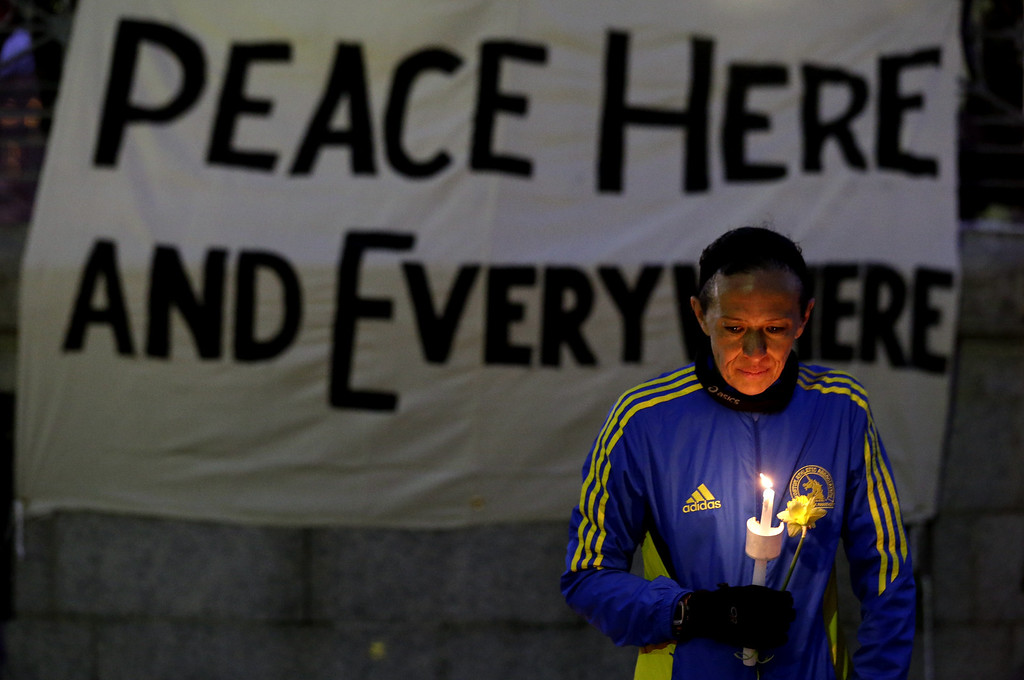 Description of . Lizzie Lee, 56, of Lynwood, Wash., who was participating in her first Boston Marathon and 11th overall, holds a candle and a flower at Boston Common during a vigil for the victims of the Boston Marathon explosions, Tuesday, April 16, 2013. (AP Photo/Julio Cortez)