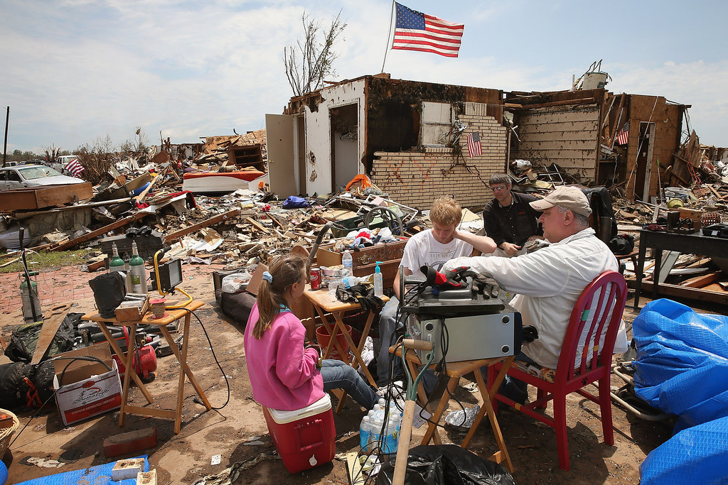 Description of . MOORE, OK - MAY 23:  Family members take a lunch break as they help Fred Martin (not pictured) recover items from his home, which was destroyed by a tornado, on May 23, 2013 in Moore, Oklahoma. A two-mile wide EF5 tornado touched down in Moore May 20 killing at least 24 people and leaving behind extensive damage to homes and businesses. U.S. President Barack Obama promised federal aid to supplement state and local recovery efforts.  (Photo by Scott Olson/Getty Images)