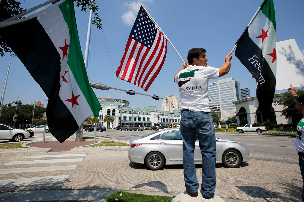 Description of . People demonstrate in support of United States involvement in the conflict in Syria on Saturday, Aug. 31, 2013 in Houston. (AP Photo/Eric Kayne)