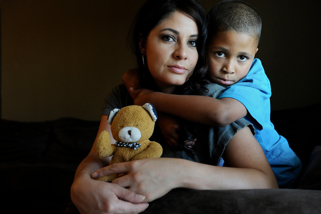 Description of . Amee Espinoza and her son, Isaiah Austin, pose for a portrait with a teddy bear that belonged to her other son, Jeremiah Saunders, at their home in Aurora, CO, Wednesday July 12, 2012. Jeremiah was at Dammi Seneviratne's Denver day care when he died on Nov. 4, 2010. When Senevirante left Jeremiah alone in the basement. The 17-month-old was rushed to Children's Hospital where he was pronounced dead. But investigators found evidence that Jeremiah sat unattended after he died, according to a state and county review of the boy's death. Craig F. Walker, The Denver Post