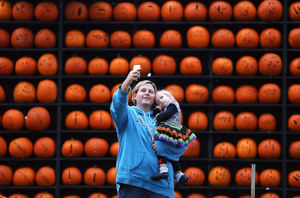 Description of . Jennifer Blake takes a photo with her daughter Reagan Blake, 2, in front of a wall of pumpkins at the Pumpkin House on Wednesday, Oct. 30, 2013, in Kenova, W.Va. (AP Photo/The Herald-Dispatch, Sholten Singer)