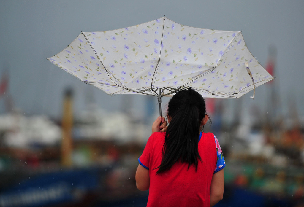 Description of . In this photo provided by China\'s Xinhua News Agency, a woman struggles with an umbrella in the strong wind at a harbor in the Luoyuan County, southeast China\'s Fujian Province, Saturday, July 13, 2013. A powerful typhoon surged across northern Taiwan on Saturday, killing at least one person before moving to southeast China and forcing the evacuation of hundreds of thousands of people from a coastal province. (AP Photo/Xinhua, Wei Peiquan)