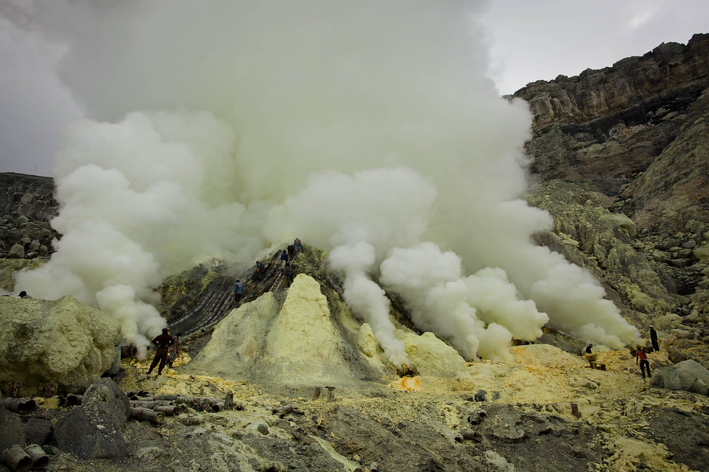 Description of . Miners extracts sulphur from pipe at the flow crater during an annual offering ceremony on the Ijen volcano on December 17, 2013 in Yogyakarta, Indonesia. (Photo by Ulet Ifansasti/Getty Images)