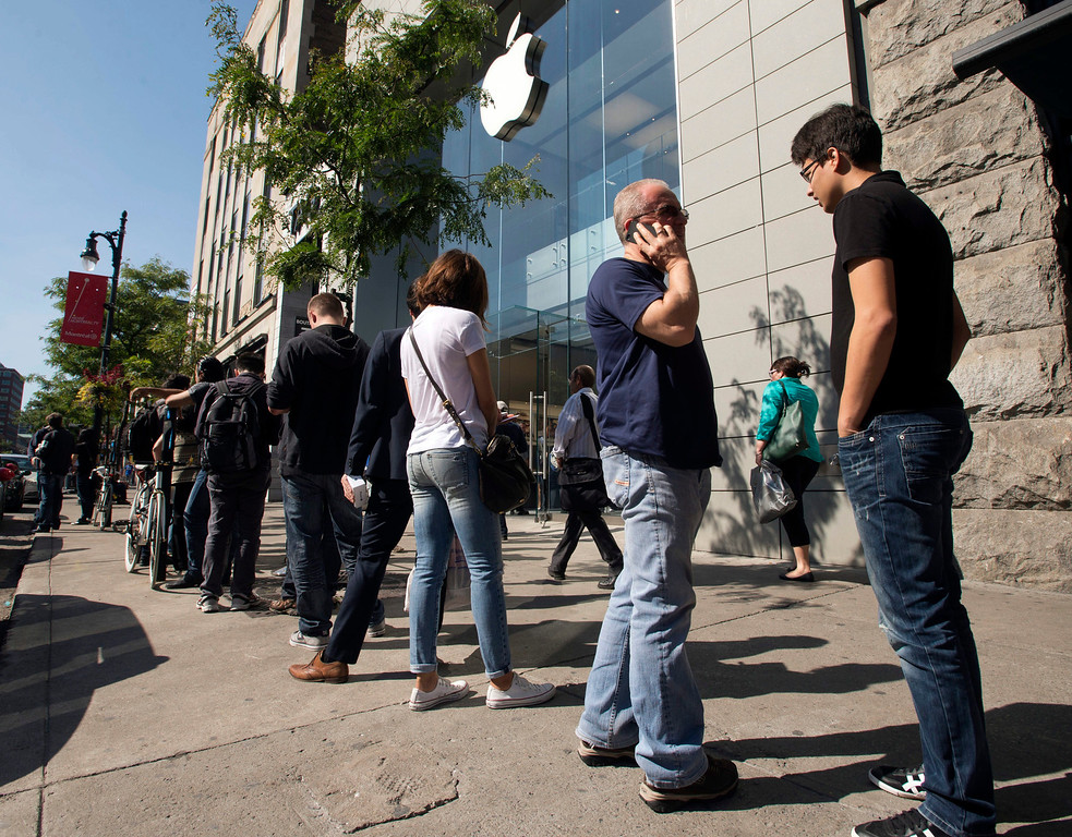 Description of . Customers  wait in line for the latest versions of the iPhone that went on sale Friday, Sept.  20, 2013 in Montreal. Friday is the first time Apple is releasing two different iPhone models at once. (AP Photo/The Canadian Press, Ryan Remiorz)