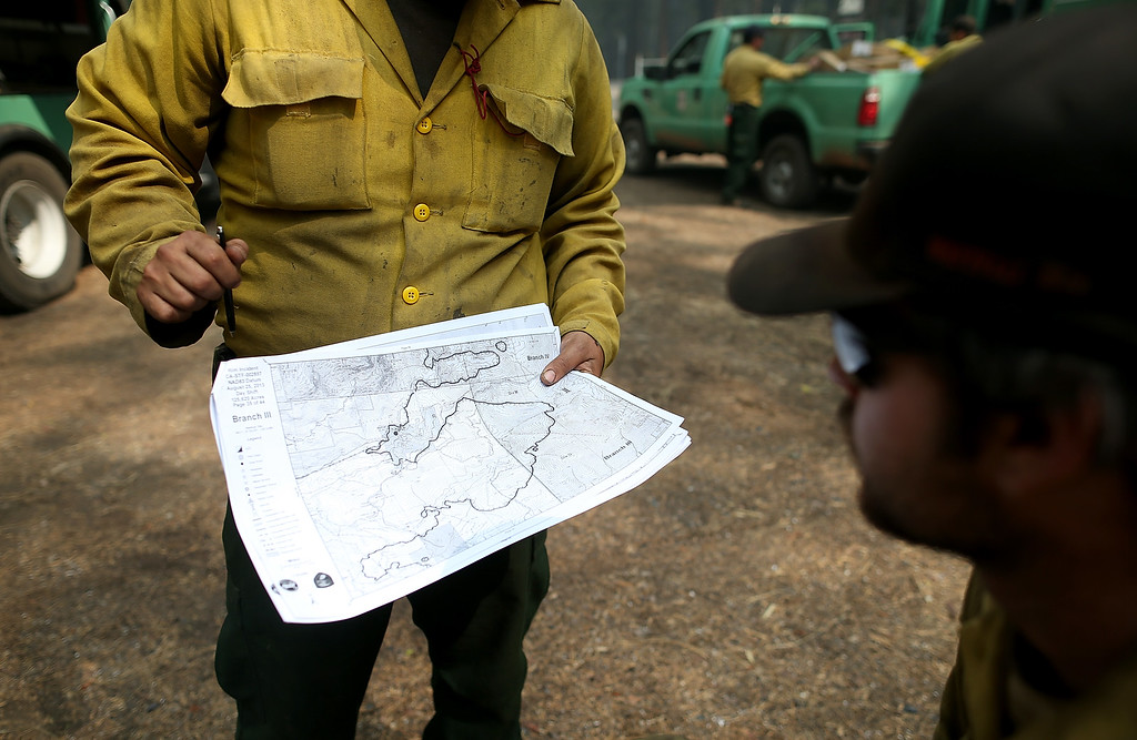 Description of . U.S. Forest Service firefighters look at an incident map as they take a break from battling the Rim Fire at Camp Mather on August 25, 2013 near Groveland, California.  (Photo by Justin Sullivan/Getty Images)