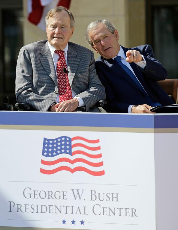 Description of . Former President George W. Bush talks with his father, former President George H. W. Bush, left, during the dedication of the George W. Bush Presidential Center, Thursday, April 25, 2013, in Dallas. (AP Photo/David J. Phillip)