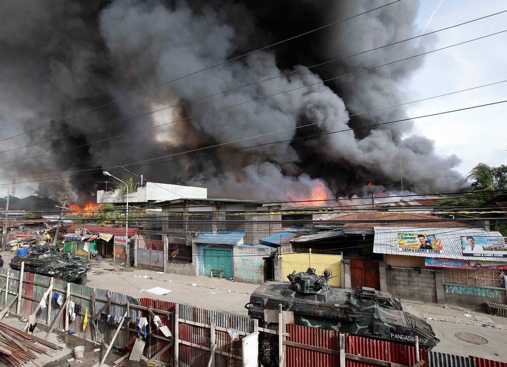 Description of . Several houses are gutted by fire as government troopers continue their assault at Muslim rebels Thursday, Sept. 12, 2013 in Zamboanga city in southern Philippines.  (AP Photo/Bullit Marquez)