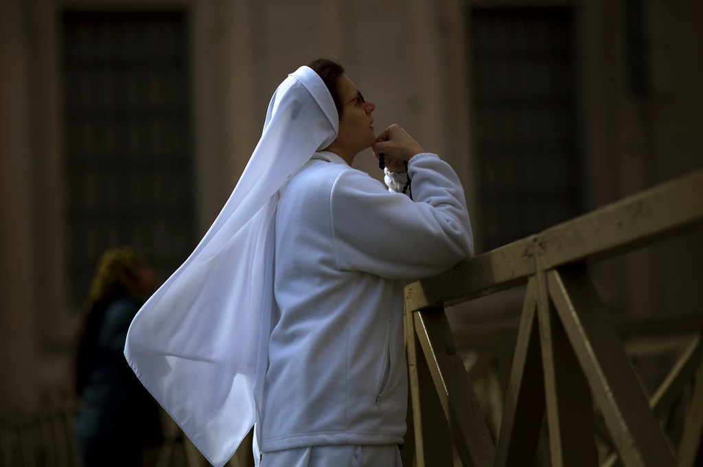 Description of . A nun prays inside St. Peter\'s Square, at the Vatican, Tuesday, March 12, 2013. Cardinals enter the Sistine Chapel on Tuesday to elect the next pope amid more upheaval and uncertainty than the Catholic Church has seen in decades: (AP Photo/Emilio Morenatti)