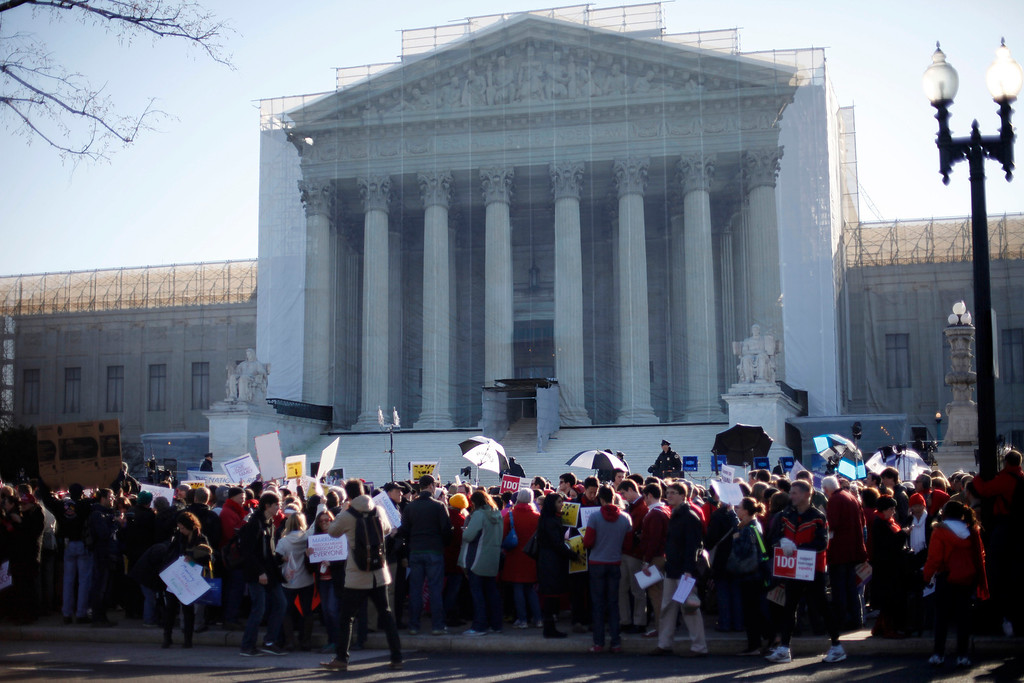Description of . Demonstrators stand outside the Supreme Court in Washington, Tuesday, March 26, 2013, where the court will hear arguments on California\'s voter approved ban on same-sex marriage, Proposition 8. (AP Photo/Pablo Martinez Monsivais)