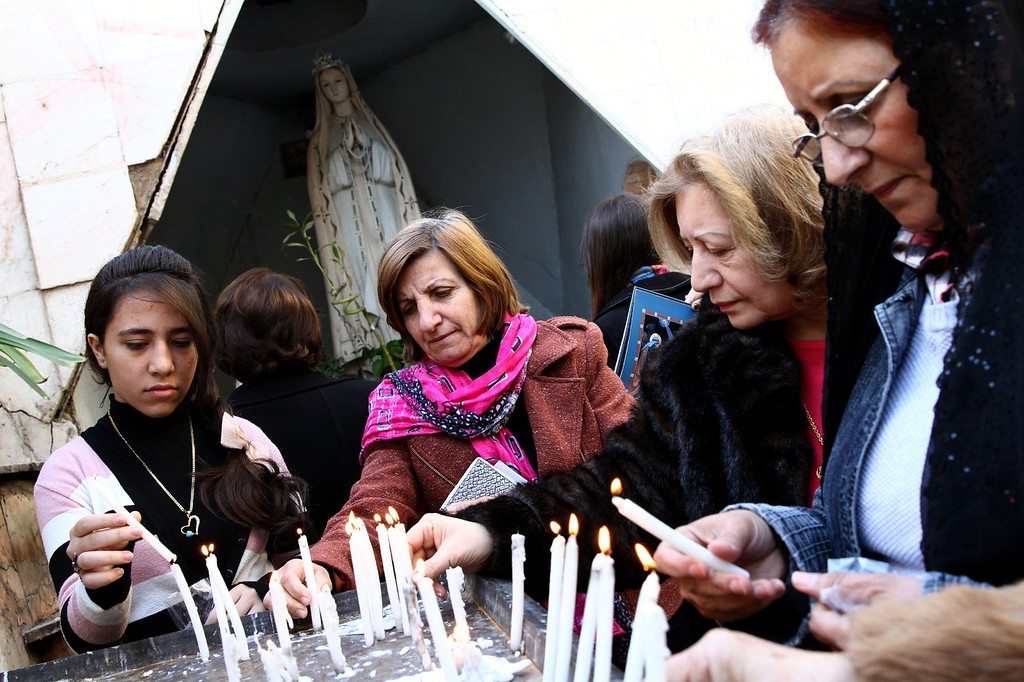 Description of . Iraqi Christians light candles as they celebrate the Christmas at the Virgin Mary Chaldean Christian church in Baghdad, Iraq, 25 December 2013. Christians comprise about 3 percent of the population in Iraq.  EPA/ALI ABBAS