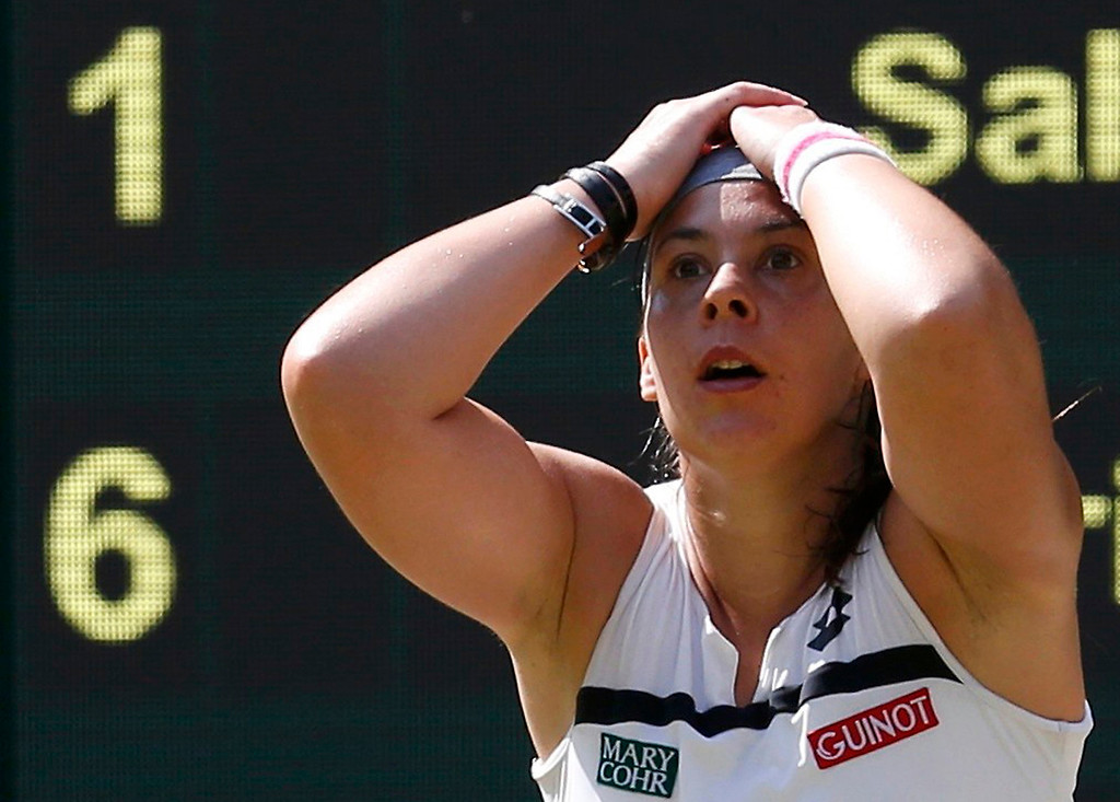 Description of . Marion Bartoli of France reacts as she defeats Sabine Lisicki of Germany in their women's singles final tennis match at the Wimbledon Tennis Championships, in London July 6, 2013.      REUTERS/Suzanne Plunkett