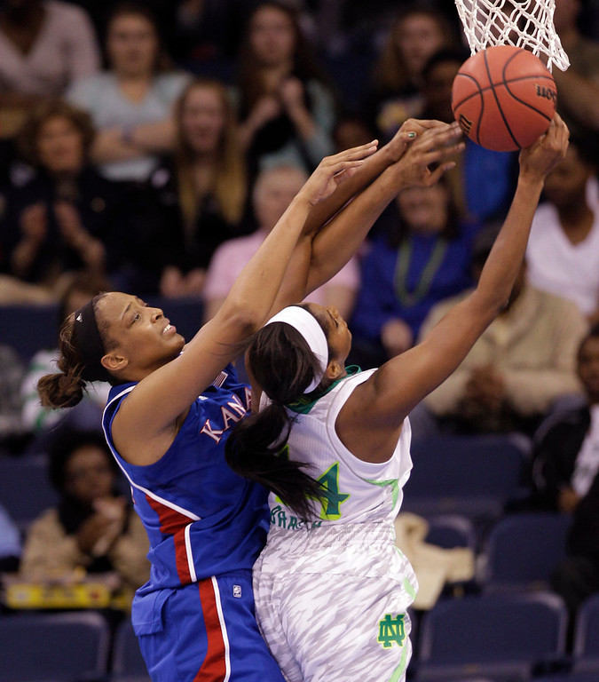 Description of . Kansas forward Carolyn Davis, left, and Notre Dame forward Ariel Braker (44) battle for a rebound during the first half of a regional semi-final of the NCAA college basketball tournament Sunday  March 31, 2013, in Norfolk, Va.  (AP Photo/Steve Helber)