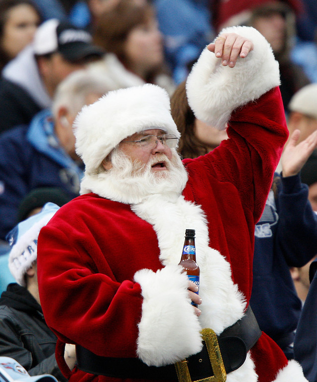 Description of . A Tennessee Titans fan dressed as Santa Claus holds his beer as he cheers in the first quarter of an NFL football game against the St. Louis Rams on Sunday, Dec. 13, 2009, in Nashville, Tenn. (AP Photo/Wade Payne)