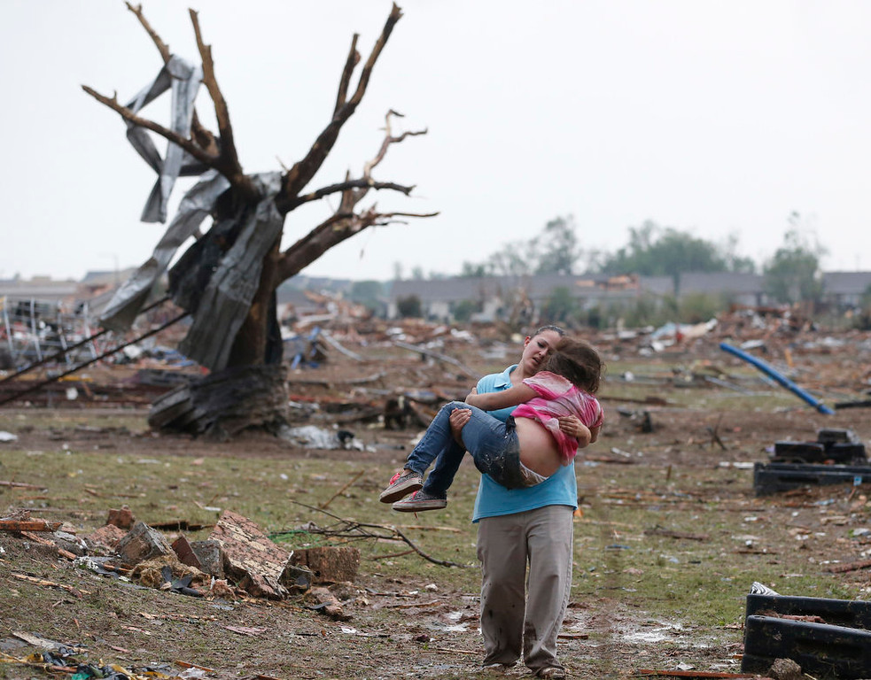 Description of . A woman carries her child through a field near the collapsed Plaza Towers Elementary School in Moore, Okla., Monday, May 20, 2013. A tornado as much as a mile (1.6 kilometers) wide with winds up to 200 mph (320 kph) roared through the Oklahoma City suburbs Monday, flattening entire neighborhoods, setting buildings on fire and landing a direct blow on an elementary school. (AP Photo Sue Ogrocki)