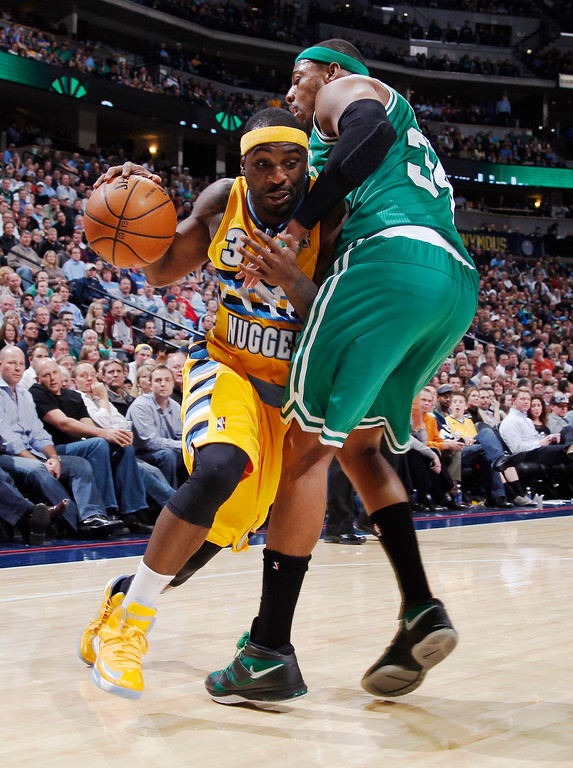 Description of . Denver Nuggets guard Ty Lawson, left, is fouled while driving to the basket by Boston Celtics forward Paul Pierce in the fourth quarter of the Nuggets' 97-90 victory in an NBA basketball game in Denver on Tuesday, Feb. 19, 2013. (AP Photo/David Zalubowski)