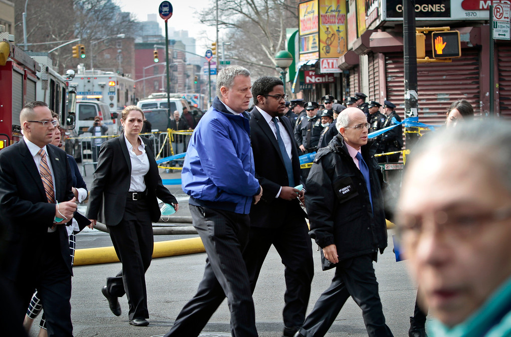 Description of . Mayor Bill de Blasio, center, arrives to visit the site of an explosion that leveled two apartment buildings in the East Harlem neighborhood of New York, Wednesday, March 12, 2014. Con Edison spokesman Bob McGee says a resident from a building adjacent to the two that collapsed reported that he smelled gas inside his apartment, but thought the odor could be coming from outside. (AP Photo/Bebeto Matthews)