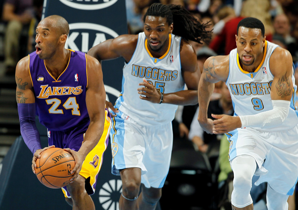 Description of . Los Angeles Lakers guard Kobe Brant, left, picks up a loose ball in front of Denver Nuggets forward Kenneth Faried, center, and guard Andre Iguodala in the first quarter of an NBA basketball game in Denver on Monday, Feb. 25, 2013. (AP Photo/David Zalubowski)