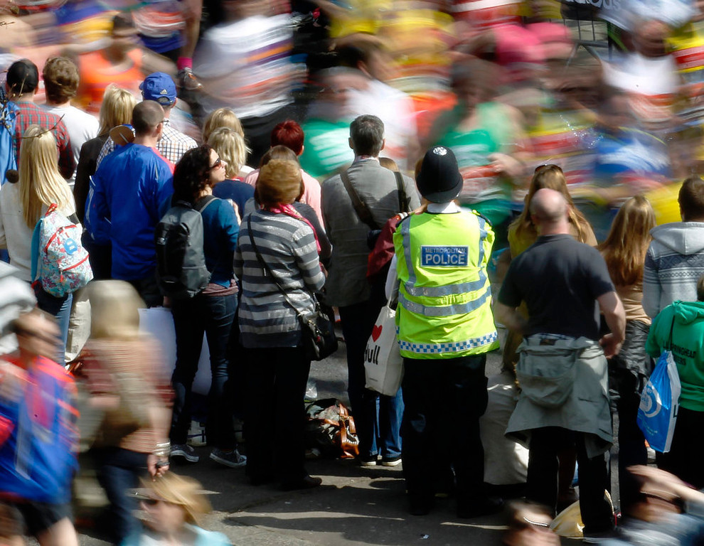 Description of . A police officer observes runners and crowd during the London Marathon April 21, 2013. Undaunted by the Boston Marathon bombings, big crowds lined the route of London 's mass road race on Sunday to cheer on around 36,000 runners, many of whom wore black ribbons to remember the dead and wounded. REUTERS/Luke MacGregor