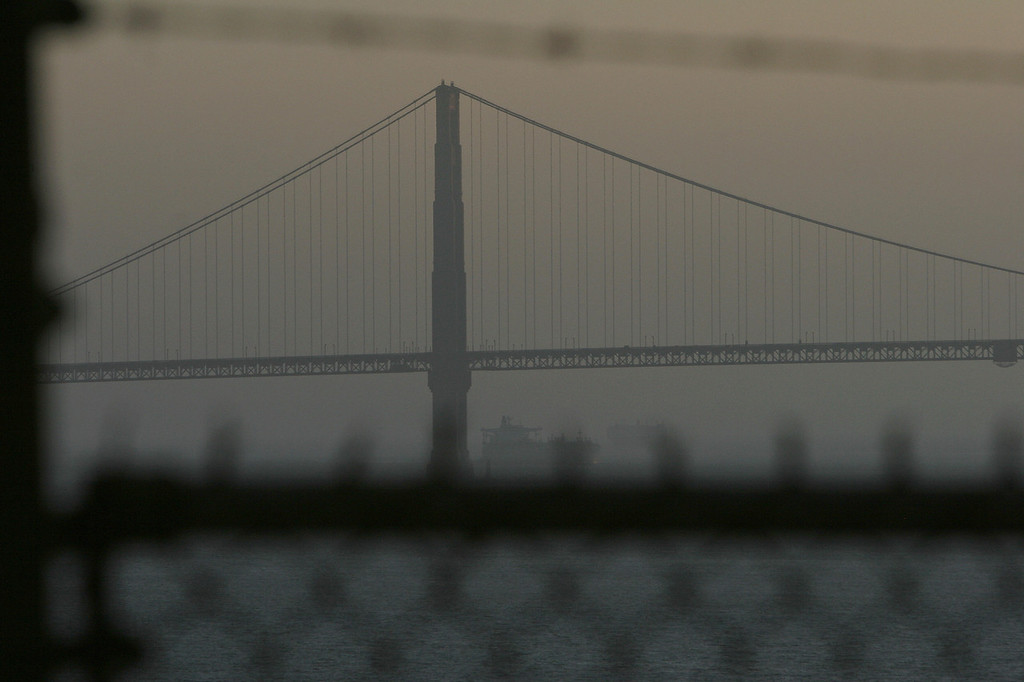 Description of . The Golden Gate Bridge is visible through the fence and barbed wire surrounding the prison recreation yard as the sun sets on Alcatraz Island, 14 June 2007 in San Francisco Bay of California. (ROBYN BECK/AFP/Getty Images)