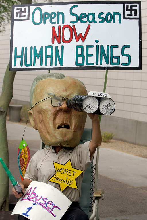 Description of . Looking through papier-mache binoculars, Jorge Mendez, of Phoenix, is dressed up to depict Maricopa County Sheriff Joe Arpaio as he joins dozens to protest the SB1070 Arizona immigration law in front of U.S. District Court Thursday, July 22, 2010, in Phoenix.  U.S. District Judge Susan Bolton is holding multiple hearings on whether the new Arizona immigration law should take effect on July 29. (AP Photo/Ross D. Franklin)