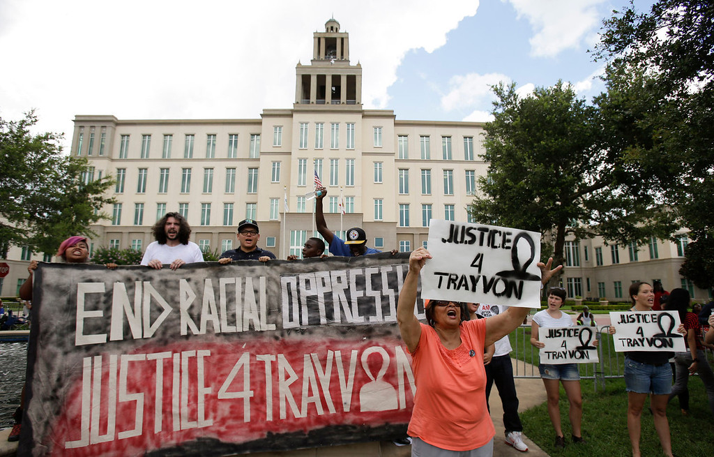 Description of . Demonstrators shout slogans in front of the Seminole County Courthouse during jury deliberations in the trial of George Zimmerman, Saturday, July 13, 2013, in Sanford, Fla. Zimmerman has been charged with the 2012 shooting death of Trayvon Martin. (AP Photo/John Raoux)