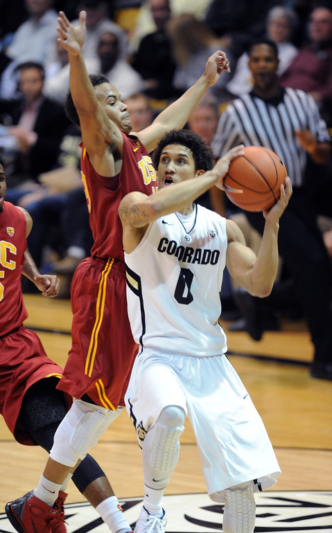 Description of . Askia Booker of Colordo drives on Chass Bryan of USC during the second half of the January 10, 2013 game in Boulder.   Cliff Grassmick/Daily Camera