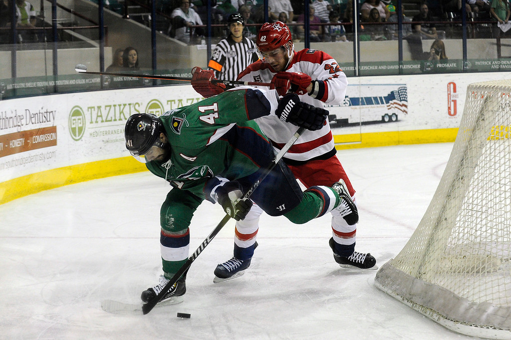 Description of . DENVER, CO - MAY 2: Garett Bembridge (41) of the Denver Cutthroats is hit from behind by Ross Rouleau (42) of the Allen Americans as they battle for a loose puck behind the net during the first period of game 1 of the Ray Miron Presidents Cup Finals at the Denver Coliseum in Denver, Colorado on May 2, 2014. (Photo by Seth McConnell/The Denver Post)