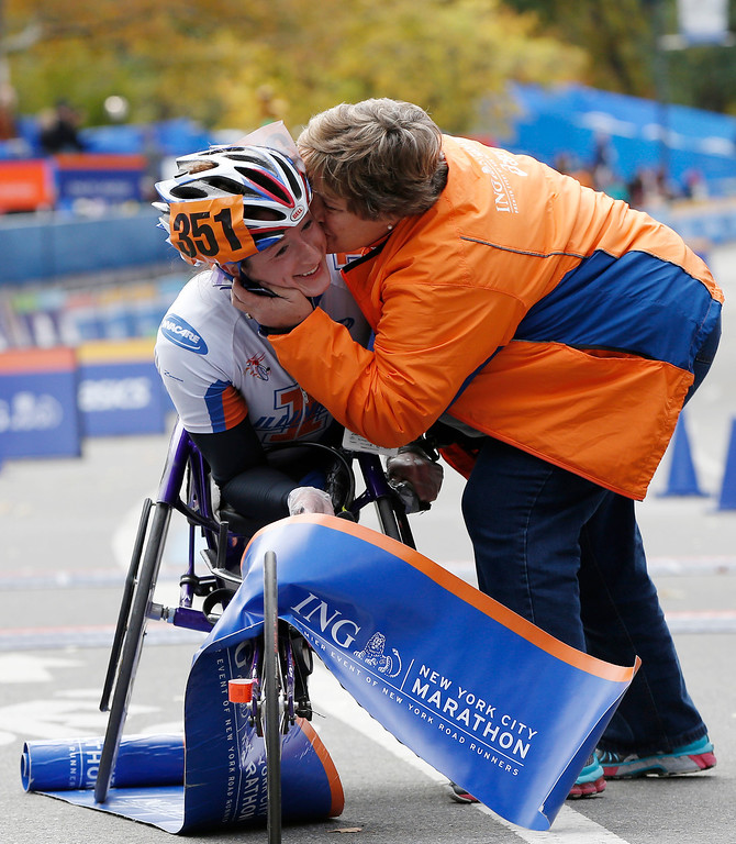 Description of . Women's wheelchair winner Tatyana McFadden, left, gets a kiss from a family member after coming in first in the women's wheelchair division of the New York City Marathon, Sunday, Nov. 3, 2013, in New York. (AP Photo/Kathy Willens)