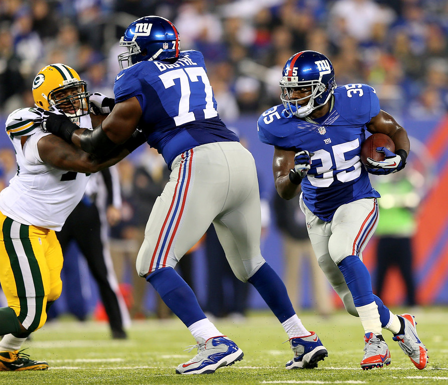 Description of . Andre Brown #35 of the New York Giants carries the ball as  Kevin Boothe #77 blocks against the Green Bay Packers at MetLife Stadium on November 17, 2013 in East Rutherford, New Jersey.  (Photo by Elsa/Getty Images)