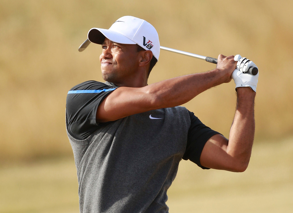 Description of . Tiger Woods of the United States plays a shot on the 12th fairway during the third round of the British Open Golf Championship at Muirfield, Scotland, Saturday July 20, 2013. (AP Photo/Peter Morrison)