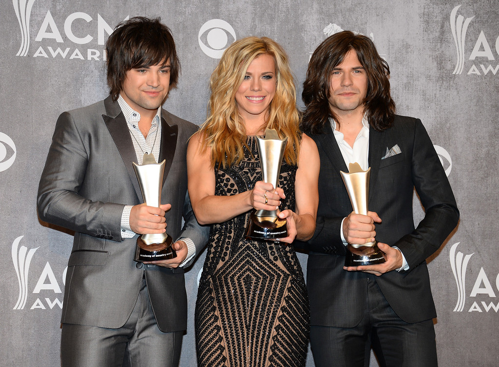 Description of . Dave Haywood, and from left, Hillary Scott and Charles Kelley, of the musical group Lady Antebellum, pose in the press room with the award for vocal group of the year at the 49th annual Academy of Country Music Awards at the MGM Grand Garden Arena on Sunday, April 6, 2014, in Las Vegas. (Photo by Al Powers/Powers Imagery/Invision/AP)