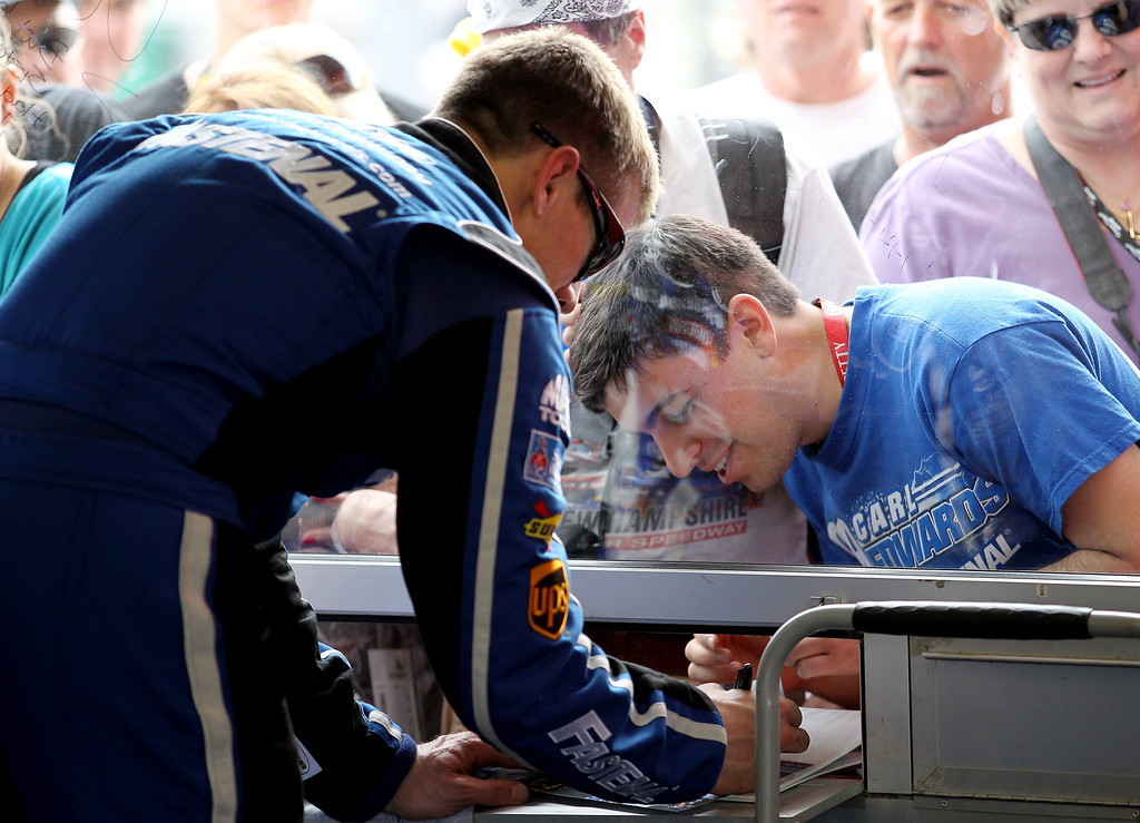 . DAYTONA BEACH, FL - FEBRUARY 20:  Carl Edwards, driver of the #99 Fastenal Ford, signs autographs in the garage area during practice for the NASCAR Sprint Cup Series Daytona 500 at Daytona International Speedway on February 20, 2013 in Daytona Beach, Florida.  (Photo by Todd Warshaw/Getty Images)