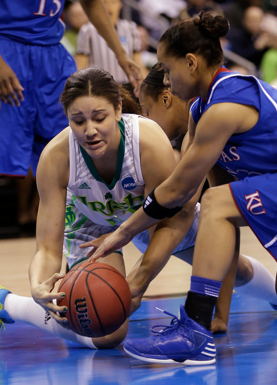 Description of . Notre Dame forward Natalie Achonwa ,left, tries to claim a rebound as Kansas guard Angel Goodrich (3) reaches in during the first half of a regional semi-final of the NCAA college basketball tournament  Sunday March 31, 2013, in Norfolk, Va.  (AP Photo/Steve Helber)
