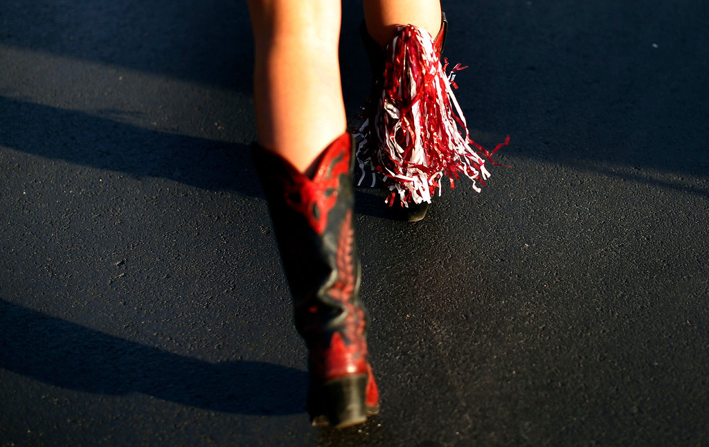 Description of . An Alabama Crimson Tide fan wears tassels on her cowboy boots outside Sun Life stadium before the BCS National Championship college football game between Alabama and the Notre Dame Fighting Irish in Miami, Florida January 7, 2013. REUTERS/Mike Segar