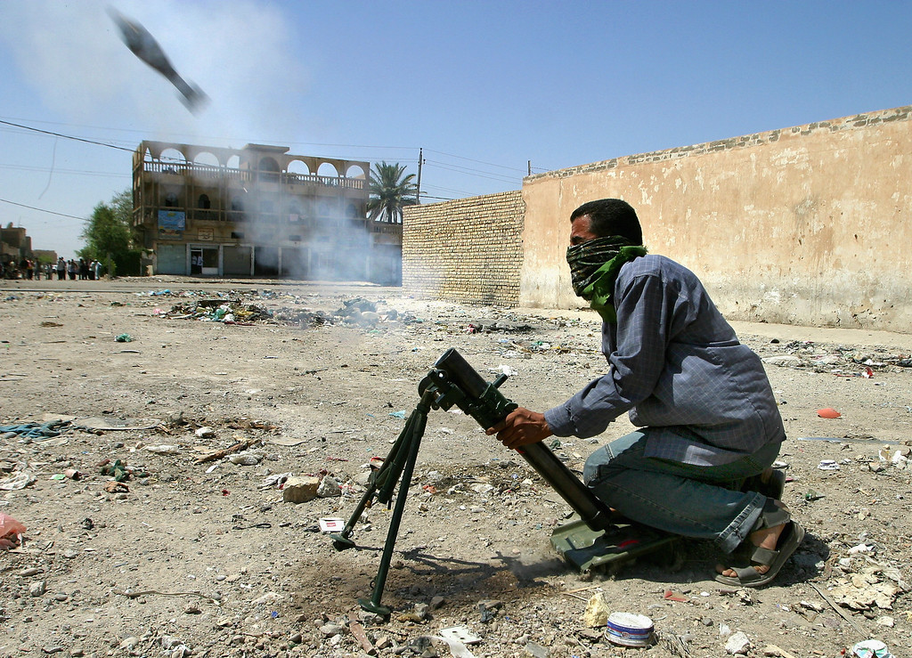 . An Iraqi militiaman loyal to the radical Shiite cleric Moqtada al-Sadr fires a mortar round during fighting between Sadr\'s Mahdi army and U.S. forces June 5, 2004 in the eastern Baghdad district of Sadr city, Iraq. Fighting continues in the capital despite a cease fire brokered between U.S. forces and the cleric\'s militia in Najaf and Kufa. (Photo by Ghaith Abdul-Ahad/Getty Images)