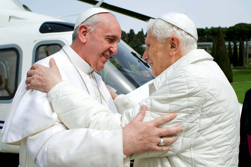 Description of . In this photo provided by the Vatican paper L'Osservatore Romano, Pope Francis meets Pope emeritus Benedict XVI in Castel Gandolfo Saturday, March 23, 2013. Pope Francis had traveled to Castel Gandolfo to have lunch with his predecessor Benedict XVI in a historic and potentially problematic melding of the papacies that has never before confronted the Catholic Church. The Vatican said the two popes embraced on the helipad. In the chapel where they prayed together, Benedict offered Francis the traditional kneeler used by the pope. Francis refused to take it alone, saying