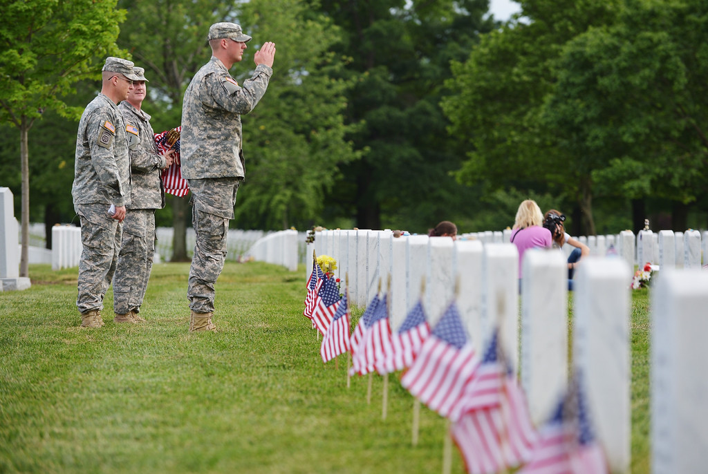 Description of . A member of the Third US Infantry Regiment, The Old Guard, salutes after placing a flag in front of a grave in Section 60 of Arlington National Cemetery on May 23, 2013 in Arlington, Virginia ahead of Memorial Day. Memorial Day is in honor of those who died while serving in the armed forces of the U.S. AFP PHOTO/Mandel NGAN/AFP/Getty Images