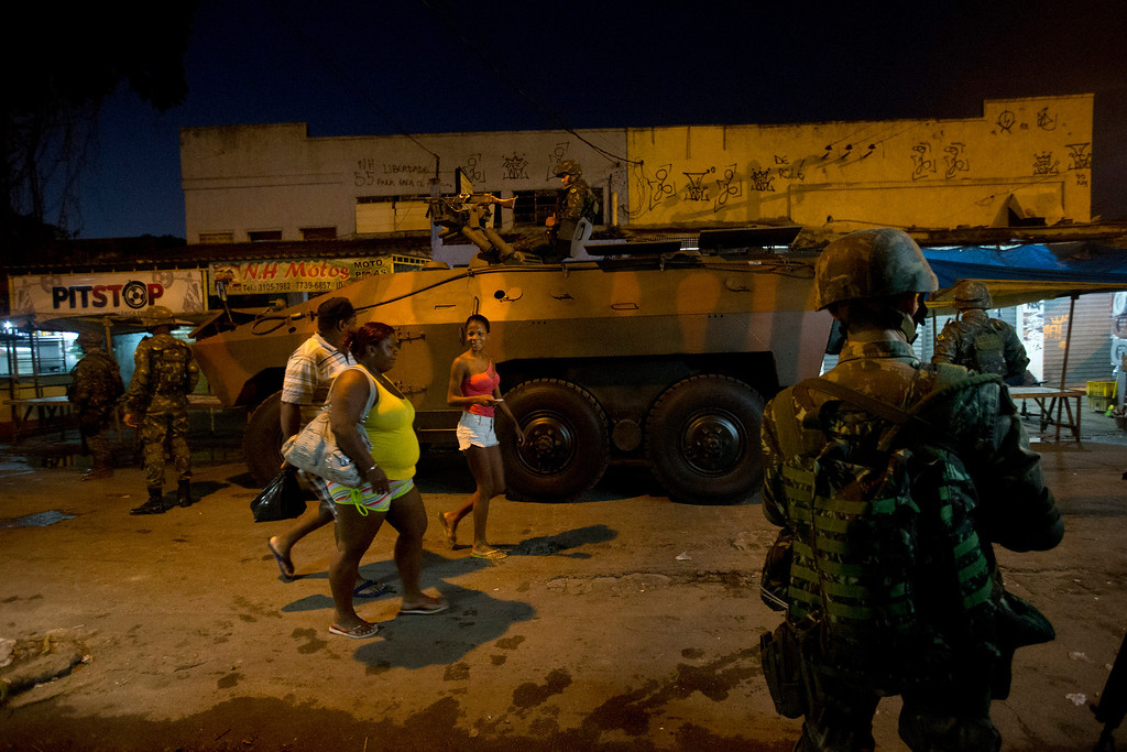 Description of . Residents walk past an armored vehicle  during an operation to occupy the Mare slum complex in Rio de Janeiro, Brazil, Saturday, April 5, 2014. More than 2,000 Brazilian Army soldiers moved into the Mare slum complex early Saturday in a bid to improve security and drive out the heavily armed drug gangs that have ruled the sprawling slum for decades. (AP Photo/Silvia Izquierdo)